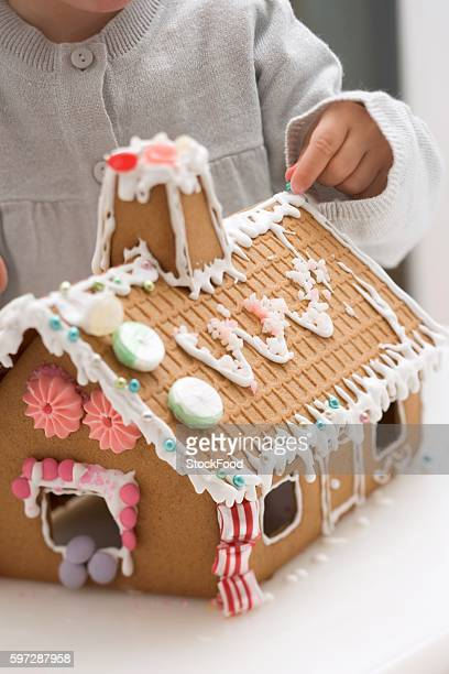 Child decorating gingerbread house with sugar pearls