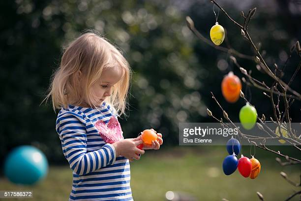 Child decorating tree with Easter eggs