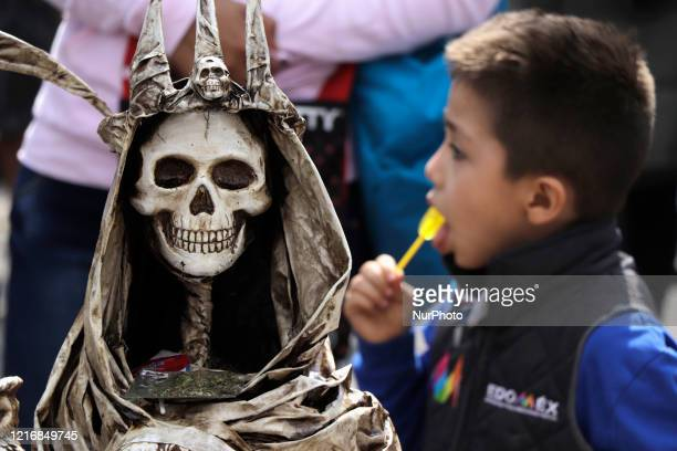 A child devoted to Santa Muerte visits the temple dedicated to this image located on Alfarería street Tepito after easing the coronavirus lockdown...
