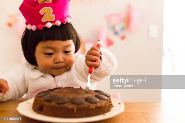 child digs a fork into her birthday cake - happybirthdaycrown stock pictures, royalty-free photos & images
