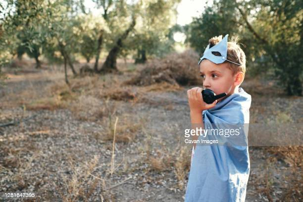 child disguised as a blue superhero takes the walkie talkie to ask for - radio stock pictures, royalty-free photos & images
