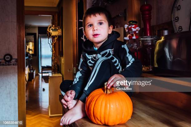 Child disguised as skeleton with a pumpkin in Halloween
