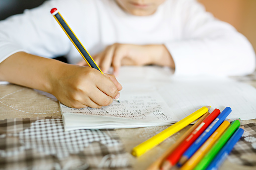 Child doing homework and writing story essay. Elementary or primary school class. Closeup of hands and colorful pencils 1083386306