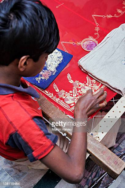 child doing rich danka embroidery work on brightly colored fabric. thin polished golden shapes are secured using gold and silver wire. usually practiced by the men from the bohra community in udaipur. rajasthan, india. - indian bohra stock pictures, royalty-free photos & images