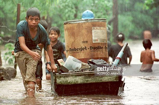 A child drags his belongings down a flooded street 31 October in Managua Nicaragua Heavy rains and severe flooding continued 31 October in Nicaragua...