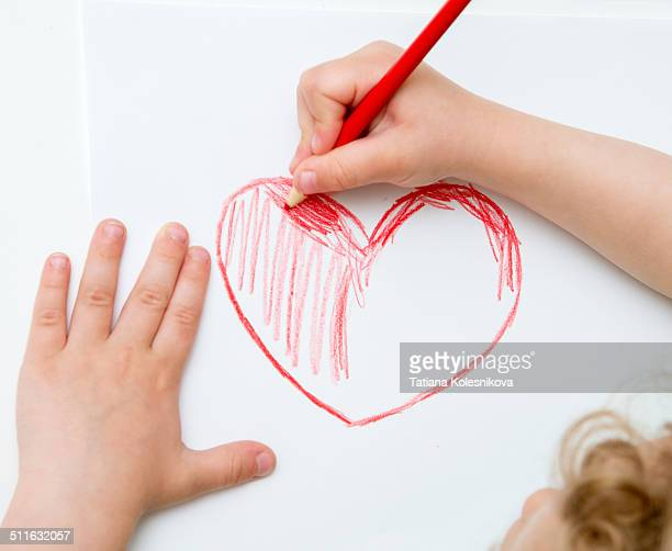 Child drawing a heart.