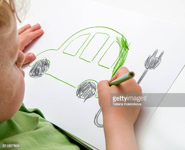 Child drawing an electric car