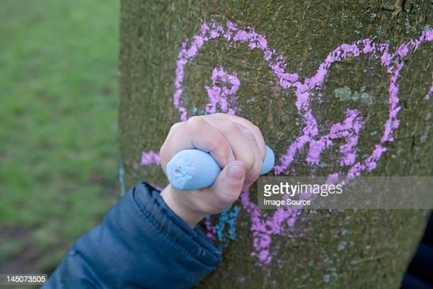 Kind zeichnen Herz auf einem Baumstamm