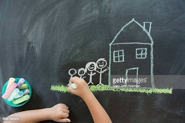 Child drawing house and family, overhead shot