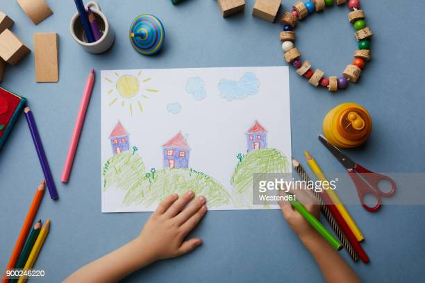 Child drawing landscape with houses