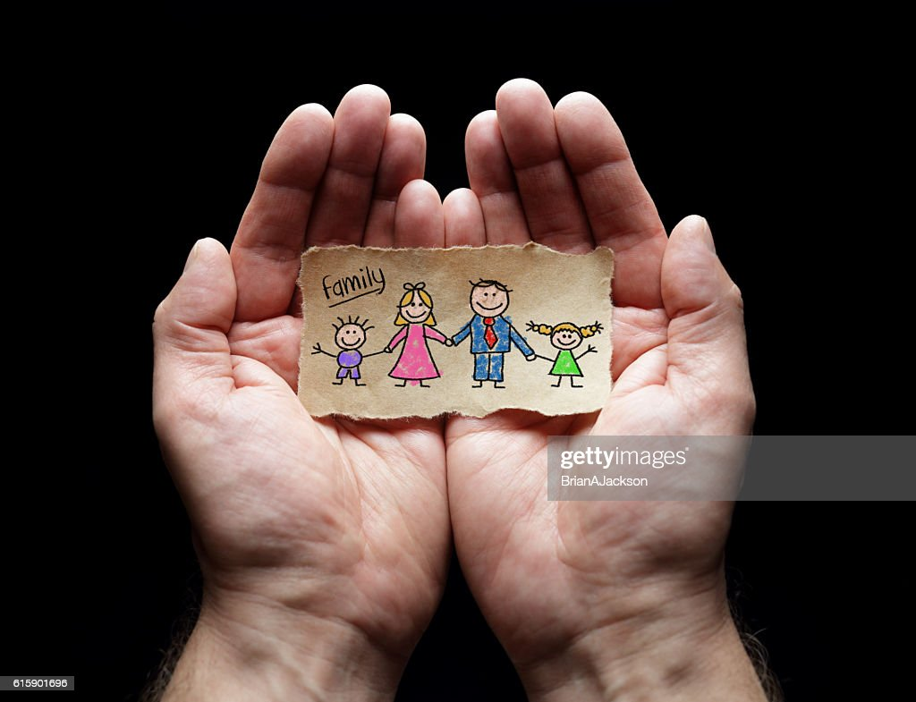 Child drawing of family with the protection of cupped hands : Stock Photo