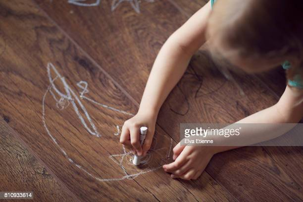 Child drawing on a hardwood floor with crayons