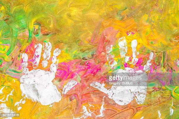 Enfant dessin peinture avec ses mains sur fond coloré blanc