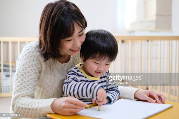 child drawing picture with mother at home - homemaker stock pictures, royalty-free photos & images