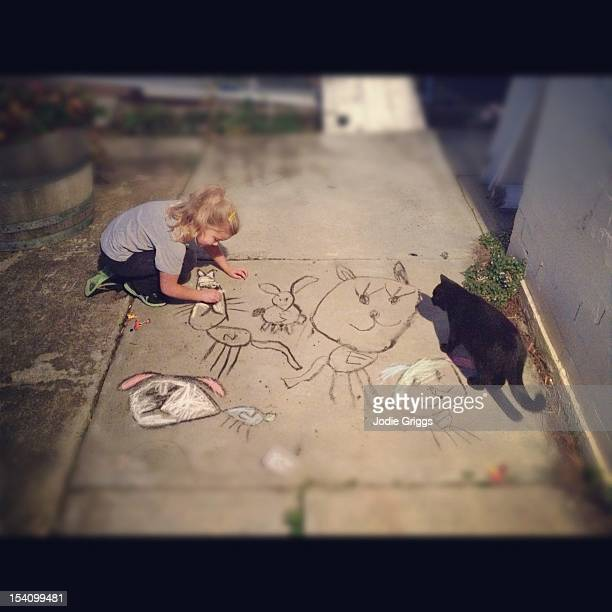 Child drawing with chalk and charcoal on pavement