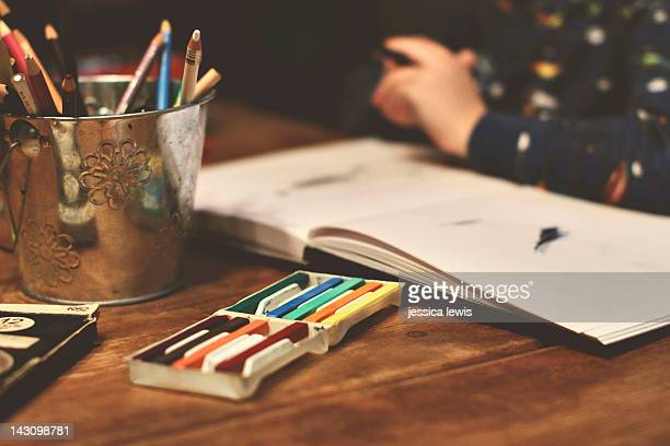 Child drawing with colored pencils