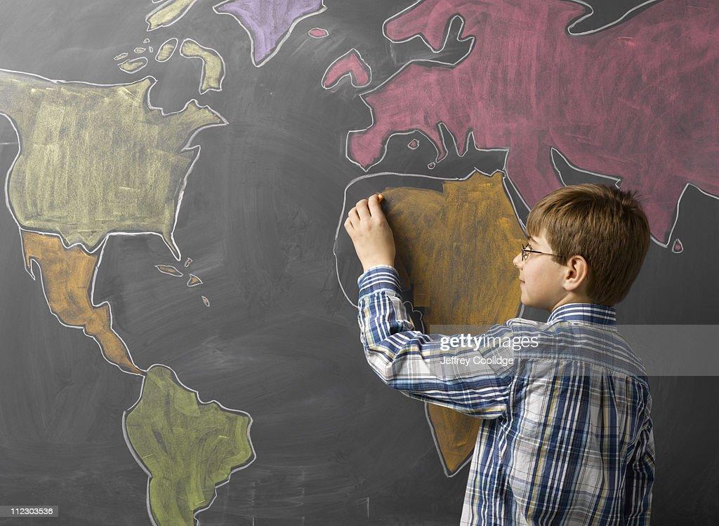 Child Drawing World Map on Blackboard : Stock Photo
