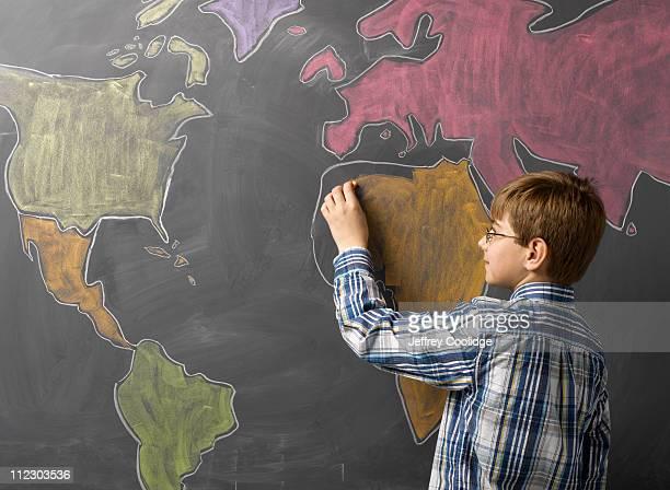 child drawing world map on blackboard - 左利き ストックフォトと画像