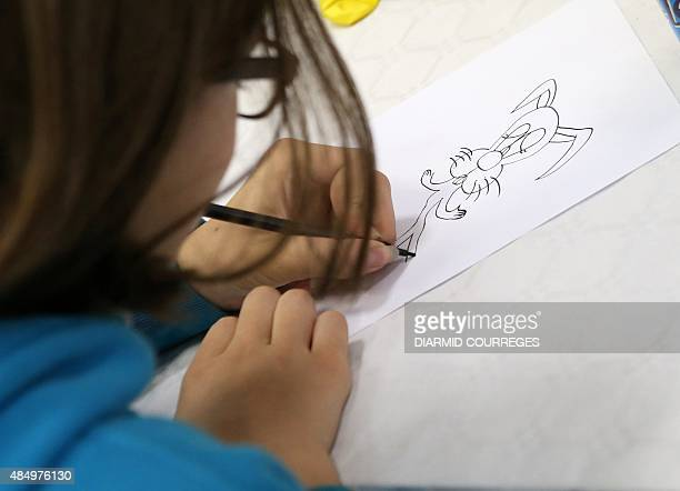 A child draws in the Salle du Pont du Buy in Brivela Gaillarde where writing and cooking workshops were organised and objets for the lefthanded were...