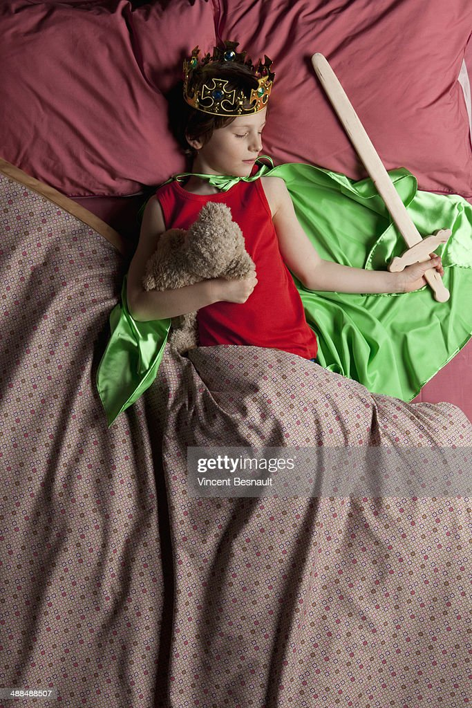 Child dressed as a king sleeping in bed : Stock Photo
