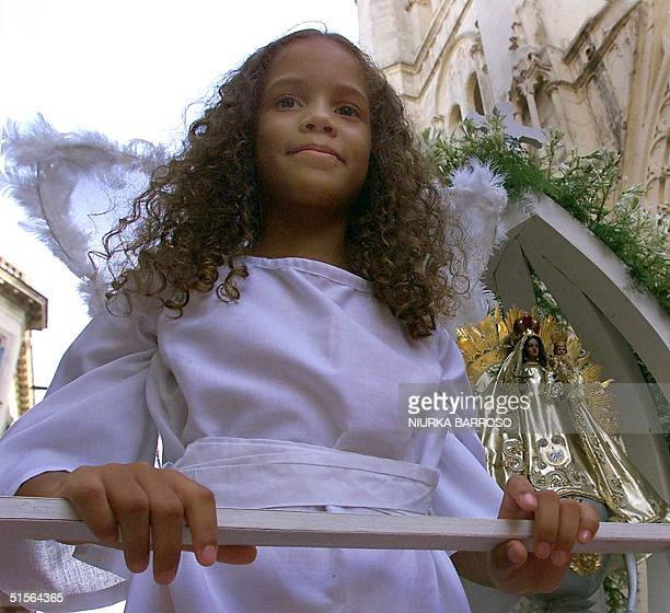 Child dressed as an angel is accompanied by an image of the Copper Virgin, during a festival, 08 September 2000, in Havana, Cuba. Hundreds of Cubans...