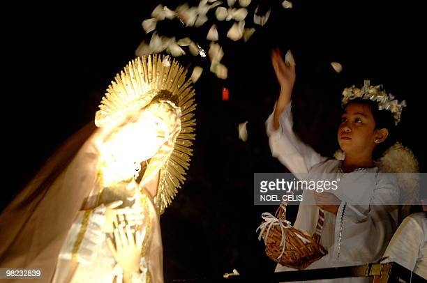 A child dressed as an angel showersthe statue of Mother Mary with rose petals during a mass in celebration of Easter Sunday outside St Domingo Church...