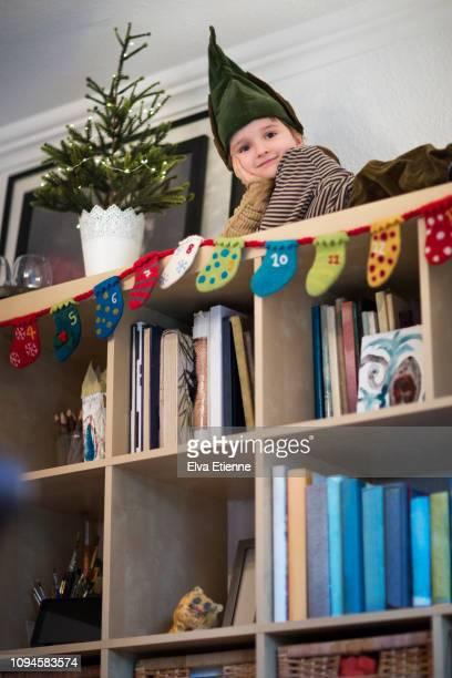 child (6-7) dressed as an elf on top of a bookshelf - advent calendar fotografías e imágenes de stock