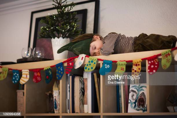 child (6-7) dressed as an elf, sleeping on top of a bookshelf - avvento foto e immagini stock