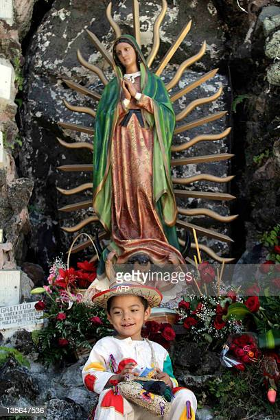 A child dressed as Juan Diego indigenous Mexican who reported the apparition of Our Lady of Guadalupe in 1531 poses in front of the statue of the...