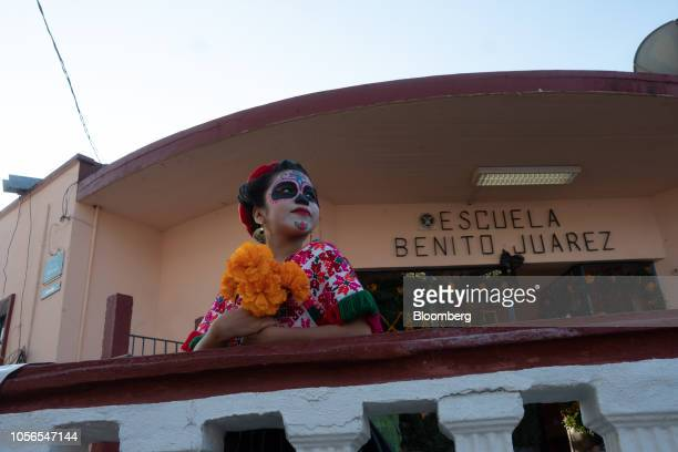A child dressed as La Calavera Catrina a highsociety skeleton lady stands in front of a school during Day of the Dead celebrations in the town of...