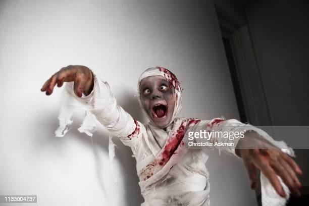 child dressed as mummy for halloween - zombie girl stock photos and pictures
