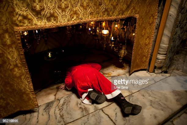 A child dressed as Santa Claus kneels at the spot in the Grotto of the Church of the Nativity where according to tradition Jesus was born as...