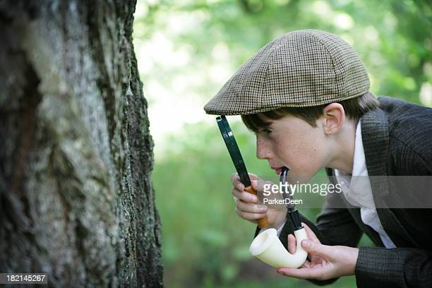child dressed as sherlock holmes uses magnifying glass in nature - sherlock holmes stock pictures, royalty-free photos & images