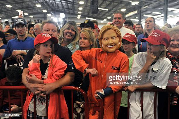 A child dressed in a mock Hillary Clinton mask and prison suit listens as Republican Presidential nominee Donald Trump addresses a capacity crowd at...