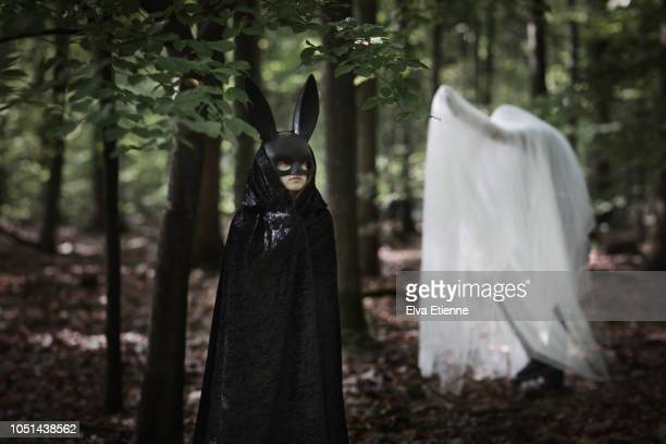 child dressed in black hooded cloak and rabbit mask watching adult dressed as halloween ghost in a dark forest - black mask disguise stock pictures, royalty-free photos & images