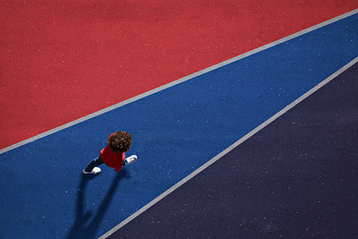 Child dressed in red, walking across red and blue painted asphalt - gettyimageskorea