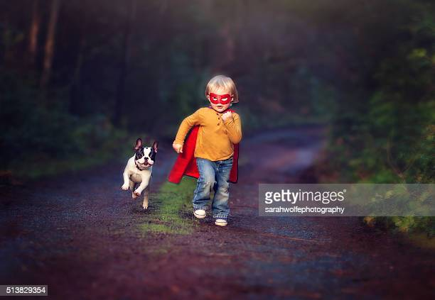 Child dressed up like a super hero with sidekick french bulldog puppy