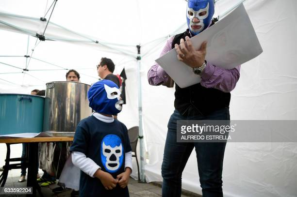 A child dressed with a mask of Mexican wrestler Blue Demon Jr waits for his autograph during a traditional event for Candelaria Day on February 2...