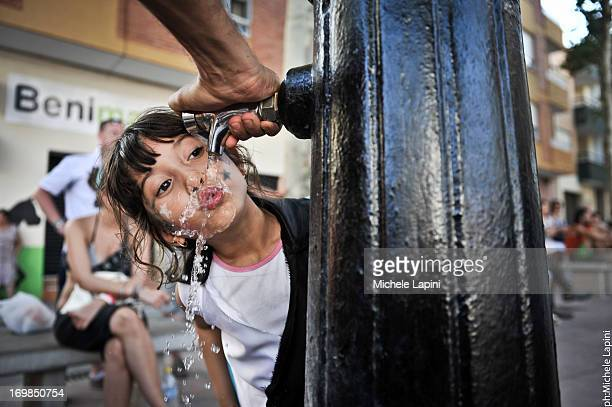 Child drink water from a public fontain in Benicassim, Spain.
