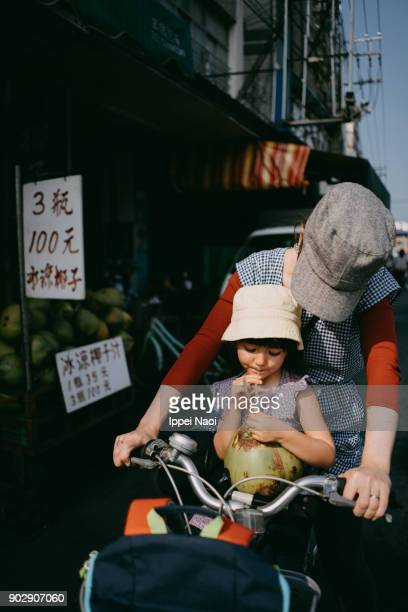 Child drinking coconut water, sitting in bicycle child seat