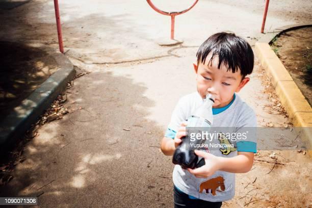 child drinking juice - yusuke nishizawa stock pictures, royalty-free photos & images