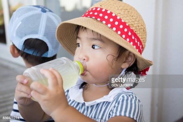 child drinking juice - 麦わら帽子 ストックフォトと画像