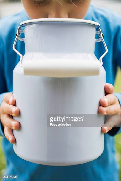 Child drinking milk out of milk can, close up, mid section