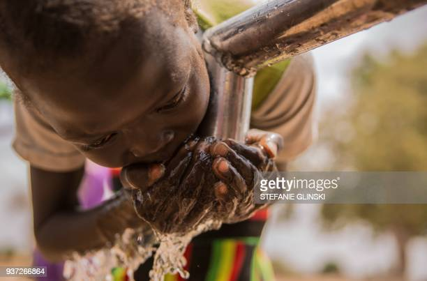 A child drinks water at a well in Nyamlel South Sudan on March 21 2018 In South Sudan households spend up to one third of their income on water...