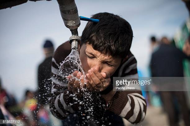 A child drinks water from a faucet while waiting a chance to cross the GreekMacedonian borderThe refugees camp on the GreekMacedonian border in...
