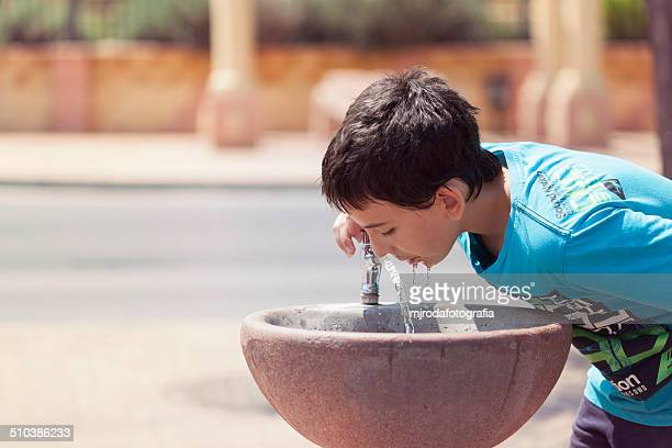 A child drinks water from a fountain