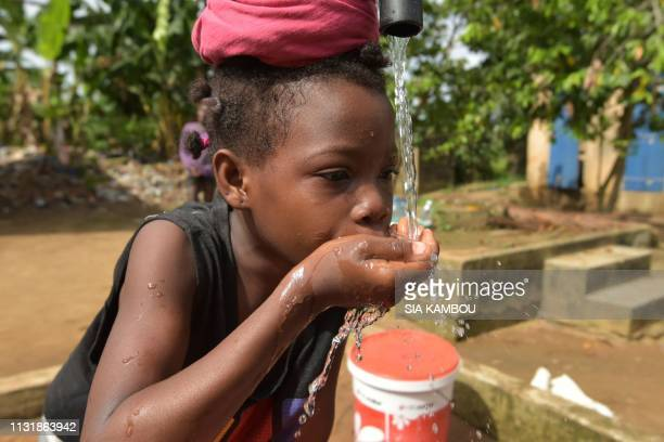 A child drinks water from a well in the popular district of Yopougon where inhabitants lack of of drinking water in Abidjan on March 21 2019 a day...
