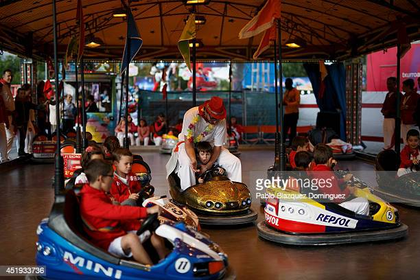 A child drives a dogem car with his father at a fair during the fourth day of the San Fermin Running Of The Bulls festival on July 9 2014 in Pamplona...