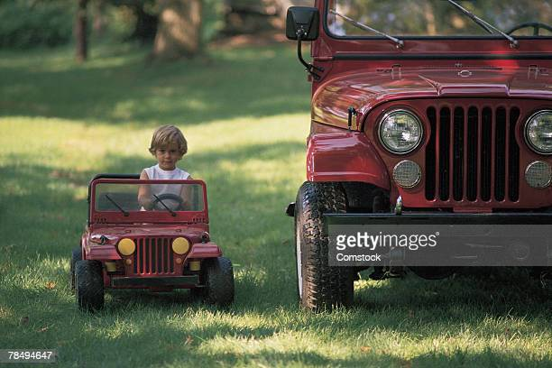 Child driving toy car next to real car