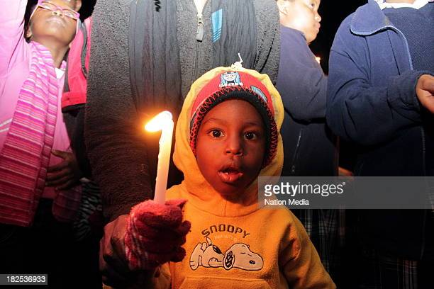 A child during prayers and tributes for the Westgate Terror attack victims on September 27 2013 outside Raybells restaurant in Nyeri town Kenya The...
